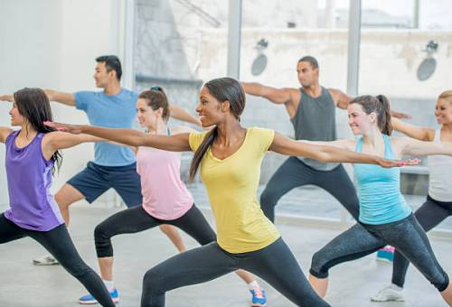A multi-ethnic group of young adults are taking a yoga class together and are holding warrior two pose.